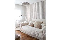 En el cuarto de la adolescente, pared de madera rústica pintada de blanco, cortinas traslúcidas con arrastre (Taupe) y lámpara de caireles. La 'Bubble Chair' de Eero Aarnio destila su aire sesentosamente lúdico.  /Magalí Saberian