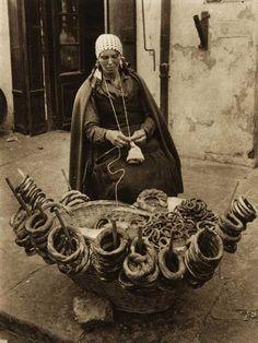 Vanzatoare-de-covrigi. Romania.  Note that  she's tensioning the yarn by running it around her neck.