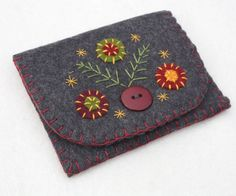 Felt coin purse with hand embroidered and appliqued flowers and leaves. Made in charcoal grey felt with a red lining, blanket stitched edges and button fastening. For coins, cards, jewellery or other
