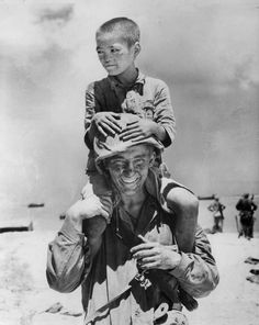 A friendly US Marine makes friends with a Japanese boy in Saipan (1944)