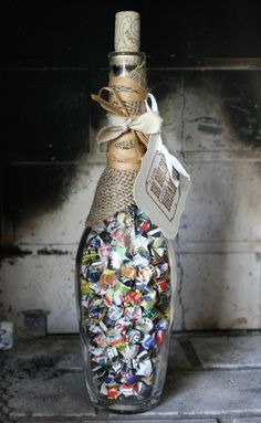 Recycled wine glass bottle with lucky origami stars made from colorful magazine pages