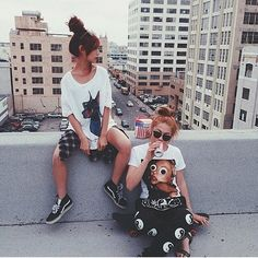 Here two very nice teenagers' skaters sit on the top of one building drinking a coke, relaxing and looking all-around of their place on the top of this building. Skaters and squatters like live together in buildings dilapidated dwellings in city centers abandoned by owners. During the summer, squatters and washers auto glass on the street corners, move into these buildings that they occupy all summer.