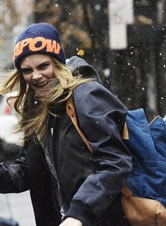 Cara Delevingne with her childhood cobalt holdall backpack slung over one shoulder