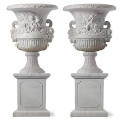 A pair of carved white marble urns on stands.