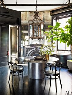 Bentwood chairs from Lee Calicchio surround the dining room's custom-made bronze table by Maison Gerard. Salvaged lantern and mantel from United House Wrecking | archdigest.com