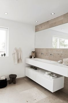 Bathroom Design Ideas - Open Shelf Below The Countertop // The shelf under the sink doesn't have to run the full length of the counter, as seen in this bright bathroom. Leaving a bit of space between the end of the shelf and the end of the counter creates the perfect spot for either a trash can or a laundry basket.