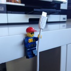 Make a Lego 'cable guy' There are lots of little plastic-ey gadgets you can buy to stop your phone and computer cables from slipping down the back of your desk. But this idea from Modernistic Design blog just seems a bit more fun. They suggest using the Lego mini figures! They also have a pic to show you how to attach your keys using Lego boards. I liked it so much I created my own 'cable guy'.