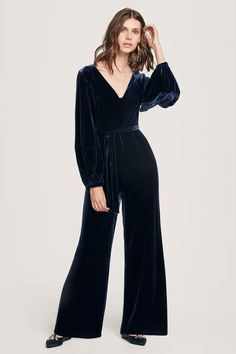 2e53beaba0f A navy velvet jumpsuit with a v-neck and long bell sleeves.