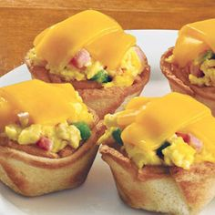 What do you get when you put bread & butter in a muffin pan, bake for 8 - 10 mins. then fill each with eggs + cheese + green peppers + ham?  You get these Ham and Cheese Toast Cups.