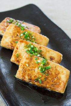 Crisp pan fried tofu with a sweet and savory glaze. 1 package medium firm tofu 1/4 tsp salt 1/4 C flour 2 Tbsp sesame oil 1 Tbsp soy sauce 1 Tbsp black vinegar (or balsamic) 1 Tbsp sugar 1 Tbsp sake 1 scallion, chopped more scallions or chives for garnish