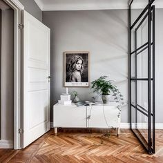Herringbone wood floor with light grey walls, white furniture and black metal glass wall