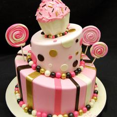 This two-tiered topsy turvy cake is topped with jumbo cupcake in an ivory wrapper with pink frosting, sprinkles and a raspberry pink cherry on top. Large r