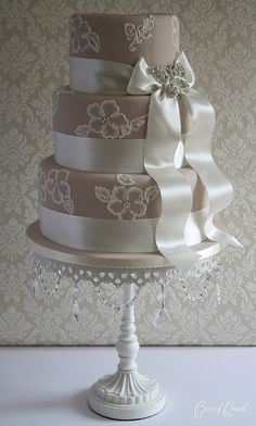 Stunning wedding cake.  Gorgeous shade of taupe with beautiful flower and ribbon detail.  Love the stand!   ᘡղbᘡ