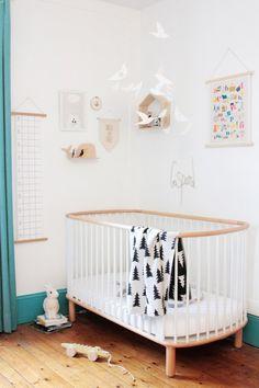 Lit évolutif scandinave (marque Flexa) blanc et bois, 3 barreaux sont amovilbles, mobile oiseaux blancs, étagères forme maison et baleine, plaid blanc motifs sapin noirs