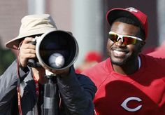The Reds' Brandon Phillips jokes with a photographer by placing a ball inside his lens during practice.