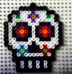 sugar skull hama bead pattern. I bet you could slap a santa hat on that pretty easily and make a cute, odd ornament for someone.