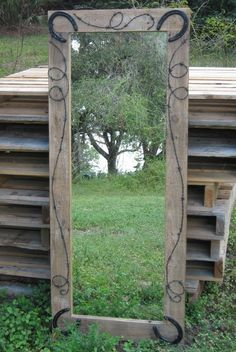 Rustic mirror DIY- frame affordable mirror with old barn wood, detail with barb wire, and old horse shoes