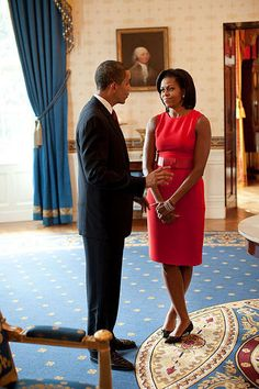 It's just another day in the White House! Here, First Lady Michelle Obama chats with her husband in an red sleeveless dress with matching belt.