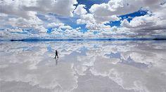 Selama musim hujan pada Februari, Salar De Uyuni, padang garam terbesar di dunia, menjadi jenuh dengan ketinggian air beberapa sentimeter memantulkan langit musim panas di atasnya.
