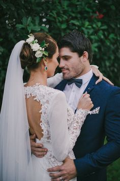 Modern bride wearing green and white flower comb and cathedral veil paired with long sleeved lace wedding dress with keyhole back, and groom wearing navy suit with polka dot bow tie | Sophie Baker Photography