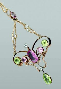 Edwardian Suffragette pendant in 9ct gold with an emerald and round brilliant cut pink tourmaline, a cushion cut peridot set to either side, a pear cut peridot, a white zircon drop and swagged with fine trace chain and seed pearls