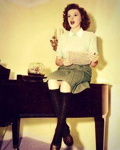 Judy Garland singing atop a piano.