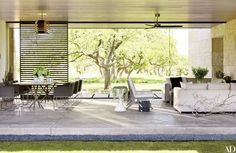 A loggia paved with sandblasted concrete links the main house to the children's wing; Sara Story designed the lounge chairs and the sofas, while the ceiling fan is by Boffi and the dining chairs are from Karkula.