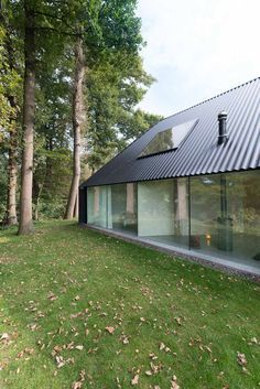 Blackened timber house with a triangular floor plan.
