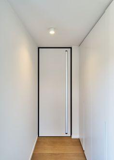 Kamerhoge witte deur met zwarte omlijsting en een verticaal ingebouwde handgreep