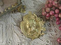 [ Antique French Brooch ]  1900年代の金属製で表面にゴールドメッキが施されたブローチです。中央に貴婦人の横顔のレリーフデザイン、縁には清楚な小花場立体的にデザインされた素敵なブローチです。