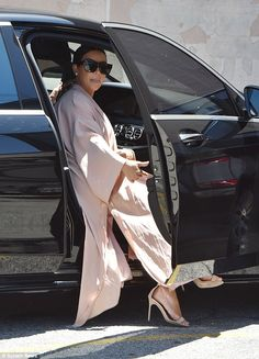 Letting it all hang out: Kim Kardashian was pictured with her coat hanging outside her moving vehicle when she left the Pantages Theater in Los Angeles on Sunday