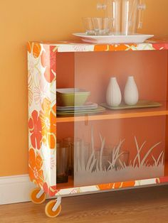A basic glass-front bookcase becomes a stellar service cart with just a roll of wallpaper.