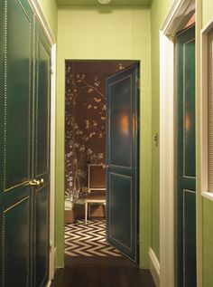 Hallway with green grasscloth & upholstered leather doors with nail head trim