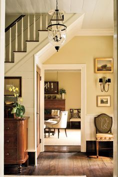 Dining Room Entry: Beautifully framed by the underside of the entry stairs, the cased opening to the dining room reveals a glimpse of the homeowners' period antiques.| Mixing period antiques with current-day style, this Georgia designer lovingly restored an 1852 farmhouse where Southern tradition lives on.