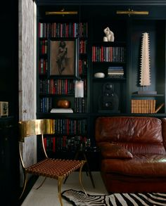 All black bookcase with leather sofa.