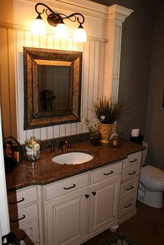 Bathroom vanity - centre sink counter bumps out with recesses drawers on either side.  bead board behind the decorative framed mirror.