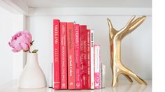 Hillary Kerr's bookshelf with pink books, a vase, and accessories // office design