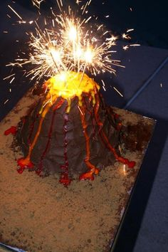 Volcano cake made from pineapple and coconut cake.  4 layers carved into the volcano shape.  Used yellow, orange and red color flow for the lava.  used brown sugar as the sand.  Stick in a few sparklers and you have a volcano.