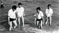 After weeks of working hard in lousy weather in Paris and New York, The Beatles frolic at Miami Beach in 1964.