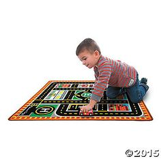 """These illustrated play rugs, each with coordinating wooden vehicles, really bring storytelling to life. Each bright, 36"""" x 39"""" woven rug features colorfully illustrated street scenes. The Emergency Vehicles Play Rug lets kids can keep the streets safe with the help of a chunky wood fire truck, police car, ambulance and helicopter. Each rug is washable, stain-resistant and durable with reinforced edges."""