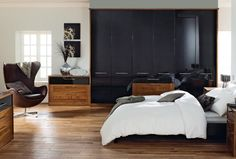 Rich and warm American black walnut style wardrobes and bedside tables bring a contemporary style to your new bedroom design.
