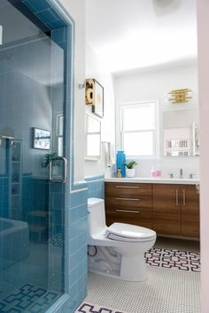 This modern and whimsical bungalow is full of surprises. Multiple styles blend well for a truly eclectic and cheery feel. Modern colors and decor can be found in every room, especially this renovated bathroom that fuses vintage blue tile with new modern elements.