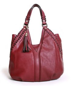 Enhance any hip handbag collection with this stylish number. Featuring a whip-stitched design and a generous interior with a zippered pocket and two pouches, it's perfect for carrying gotta-have goodies of every shape and size. Vegan leather and a tasseled accent combine to craft this chic-as-can-be tote.
