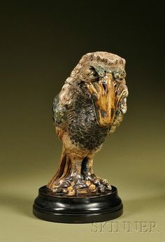 "Martin Brothers Glazed Stoneware Barrister ""Wally-Bird"" Tobacco Jar and Cover, dated 1889 and signed to cover and body, the bemused bird with curved beak and tilted slightly forward and to the right, on an ebonized wood base, ht. of bird 10 1/2, overall 12 1/2 in"