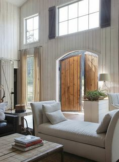 love the white wood walls, the large barn-like doors, the interior black shutters up top.