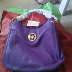 Michael Kors Shoulder Tote/MAKE OFFERS Its a gorgeous bag. Has plenty of storage places. In the middle it has a zipper part, for more storage.  Its a vibrant violet color. This bag is leather, and has golden chain on the straps, which looks awesome. It has a Michael Kors sign in front of bag. I just received this yesterday. Brand new with tags, and packing wrap still on the shoulder straps.  Make offers if you want. Michael Kors Bags Shoulder Bags