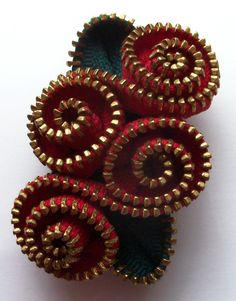 Reuse, Reduce, Recycle and  Repurpose!! Vintage zippers creatively transformed into beautiful brooches. The metal teeth highlight the colorful tapes creating a stunning affect. Completely hand sewn, no glue used.  Red petals spiral around to create this gorgeous abstract floral brooch with brass teeth which measures approximately 2.75 x 2 inches, 7 x 5 cm. It is backed with felt and has a nickel pin back. It has been signed and numbered and will arrive nestled in a white jewelers box. Thank…