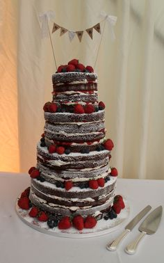 Naked wedding cake! Lots of layers, each filled with buttercream and decorated with fruit.