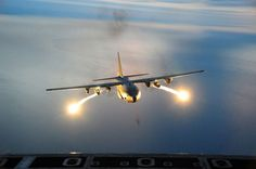U.S. Air Force C-130 Hercules cargo aircraft fires off flares during a night formation training mission