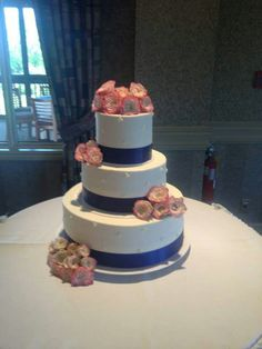 3-tier wedding cake with royal blue ribbon and accented with cream flowers edged with pink. #wedding #weddingcakes #royalblue